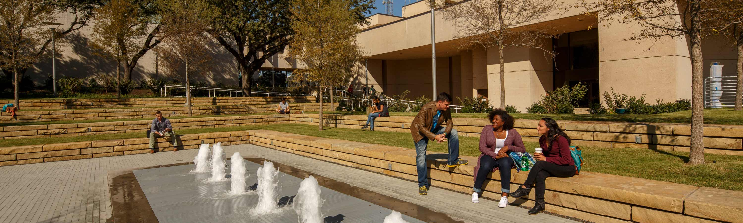 Students sitting near fountain